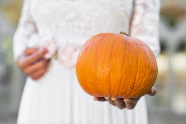 ハロウィーンの花嫁はカボチャを彼女の手に持っています