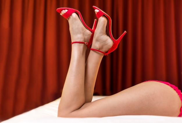 ベッドに横たわる赤いハイヒールのサンダルでスリムな完璧な女性の足。