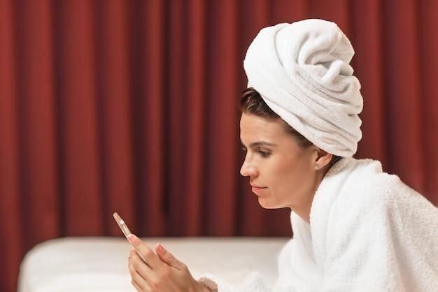ホテルの部屋に横たわっているバスローブの若い女性は、携帯電話を使用して、入浴後にリラックス