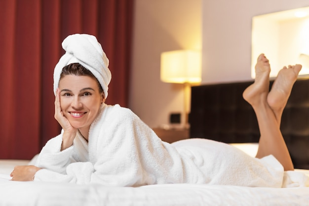 バスルームに横たわっているバスローブの若い女性、入浴後にリラックス