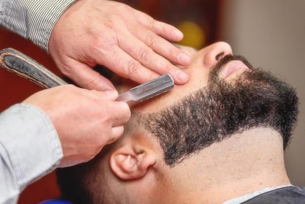 理髪店でビンテージのかみそりでひげそりを持つハンサムな男。
