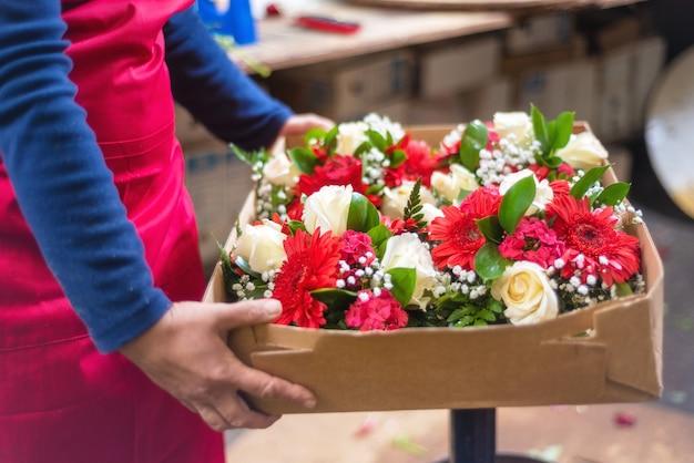 Женский флорист держит коробку с красивыми цветами для доставки.