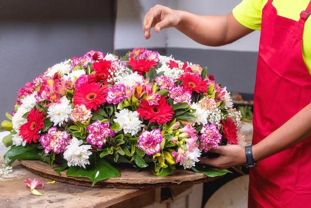 仕事で花屋。男性の花屋フラワーショップで美しい花束を作成します。