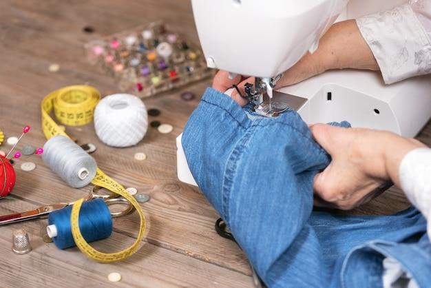 年配の女性のクローズアップは、電動ミシンで仕立て屋ミシンジーンズを手します。