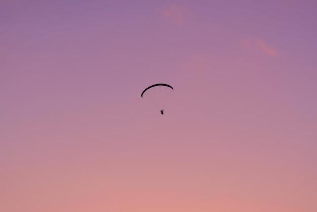 夕暮れ時にパラグライダーのシルエット