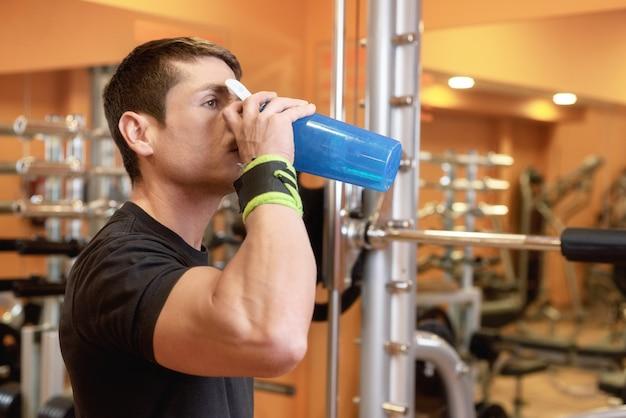 筋肉男はジムで青いボトルから水を飲む。