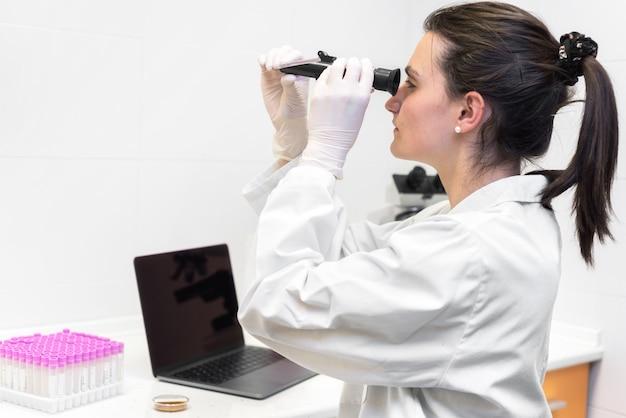 Работник лаборатории судебной экспертизы изучает образцы с помощью рефрактометра и микроскопа