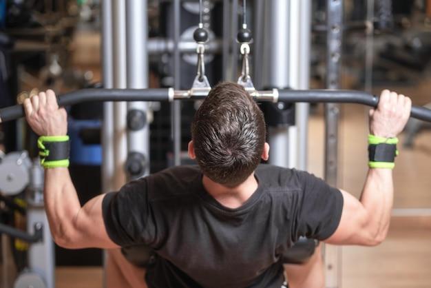 ハンドルを取り、それらを下げることによって背中の筋肉を訓練する男。強度運動のコンセプトです。