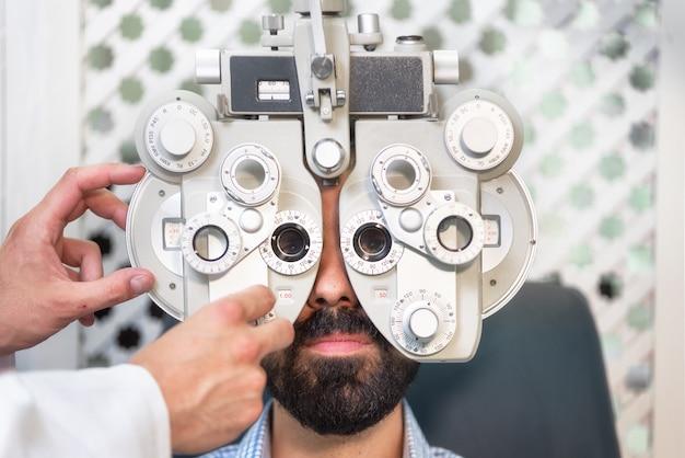 検眼医が男性患者の視力検査を行う
