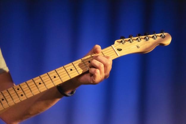 男性の手がエレキギターで遊んで、クローズアップ。