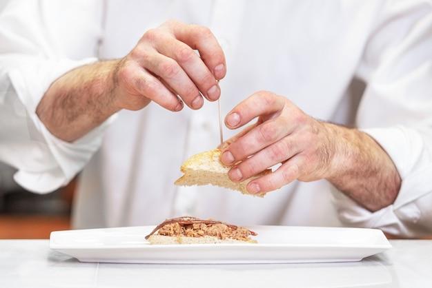 おいしい典型的なスペイン料理を準備するシェフ