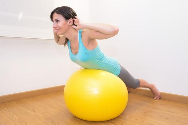 ジムでエクササイズボールでワークアウトの女性。フィットネスボールとジムのトレーニングルームでエクササイズを行うピラティス女性。