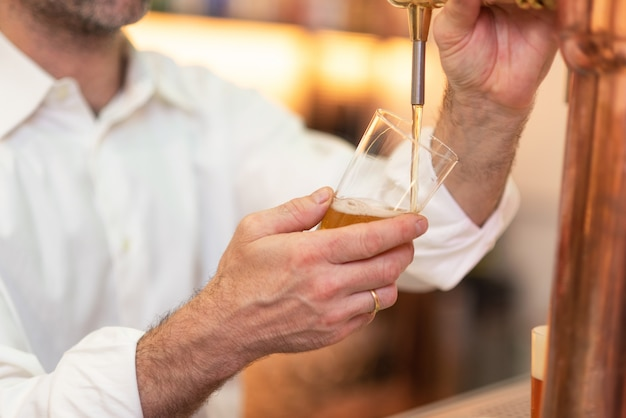 Разлив пива для клиента. бармен наливает пиво, стоя у стойки бара.