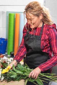Молодой женский флорист при букет работая в цветочном магазине.