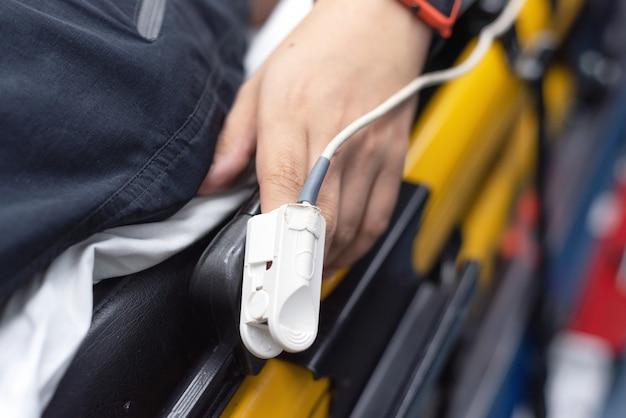 Пациент в машине скорой помощи используя пульсоксиметр пальца, контролируя жизненно важный показатель, медицинскую концепцию.