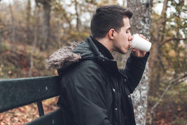 秋の公園で使い捨てのコーヒーカップを保持しているベンチに座っている若い男。