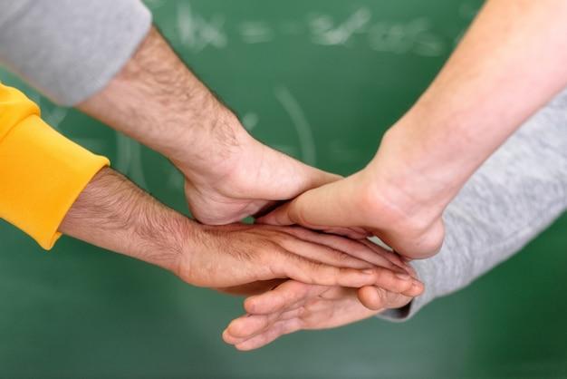 Студенты кладя руки совместно в коллеж с классн классным на заднем плане.