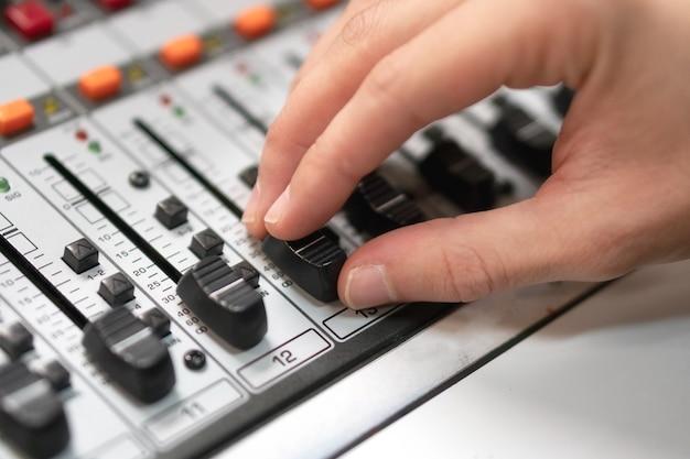 コンソール上のコントロールフェーダーの男性の手。エンジニアまたは音楽プロデューサーと録音スタジオのミキシングデスク。