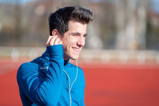 イヤホンに入れてハンサムな陽気な若い男性ランナー。