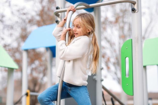 かなり、小さな女の子が子供の遊び場で遊んで、ポールでスライドする準備ができています。