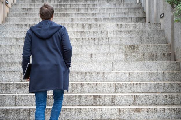 若い男が階段を屋外に歩いてコンピューターラップトップを保持しています。