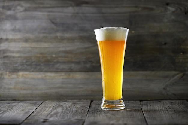 木材の背景にガラスのビール。