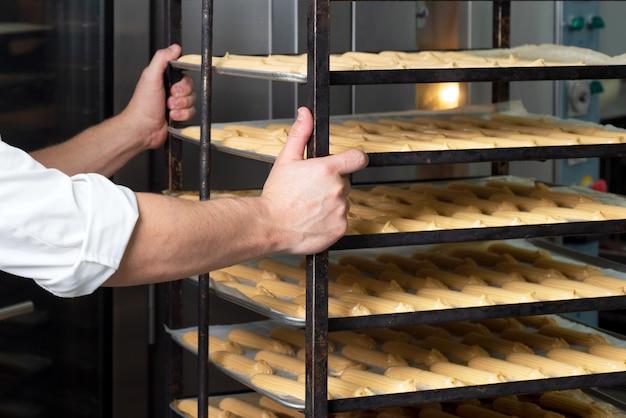 菓子工場の労働者がペストリーでトレイラックを押します。
