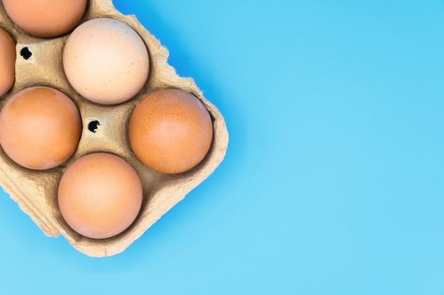 青の背景に生の茶色の鶏の卵。