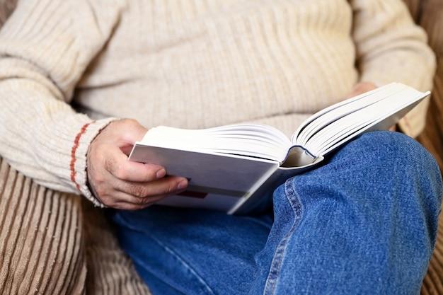 Закройте вверх по взгляду пожилого человека читая книгу, пока карантин дома.