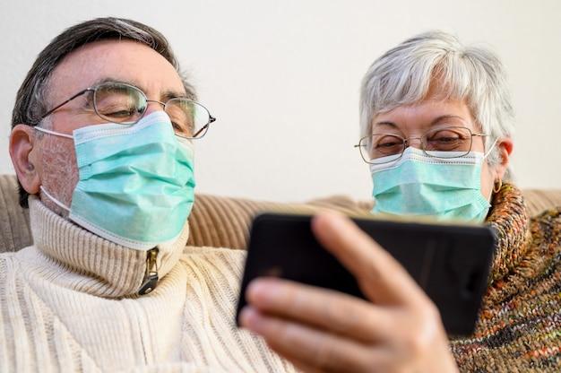 コロナウイルス。家にいる、ライフスタイル。陽気な老夫婦が自宅の検疫のソファーに座って、スマートフォンでビデオ通話をする。防護マスクを着ている年配のカップル。