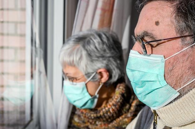 防護マスク、自宅で窓から見ている年配のカップル。コロナウイルス検疫の概念は家にとどまり、社会的距離を置く。