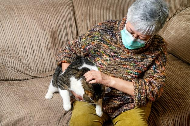 パンデミック発生によるコロナウイルスの社会的距離。防護マスクをした高齢者の女性、在宅で彼女の猫をなでます。