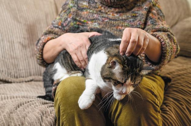 До неузнаваемости старуха гладит кота.