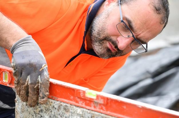 Рабочий-строитель проверяя уровень пузыря пока работающ на строительной площадке. строительство зданий.