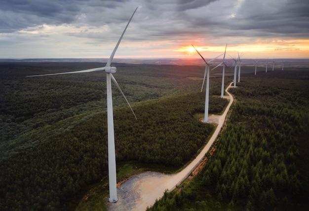 夕暮れ時の美しい森の風景に風力タービンファーム。緑の生態学的世界のための再生可能エネルギー生産。夜の山の風車農場公園の空撮。