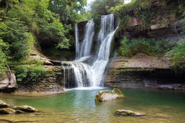Идиллический дождевой лес водопад, поток течет в пышные зеленые леса.