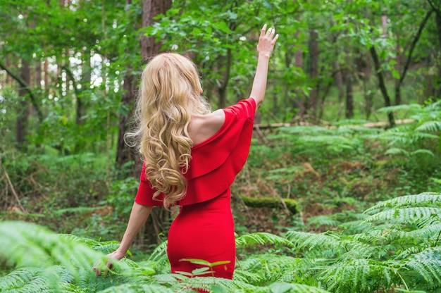 Вид сзади красивая блондинка в шикарном красном платье, касаясь папоротника в сказочном лесу. атмосфера фантастическая.