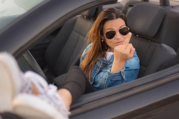 無料の女性は中指を彼女のコンバーチブル車を楽しんでいることを示しています。自由女性概念。