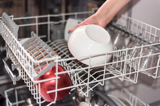Крупным планом взгляд на руку женщины, погрузка посудомоечной машины.