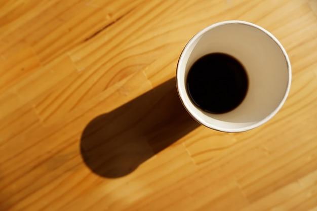 朝の光とテーブルの上のコーヒーの紙コップ