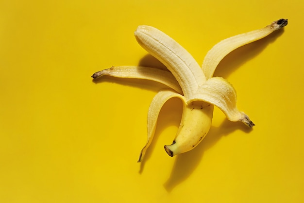 皮をむいたバナナの黄色の背景