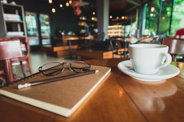 クローズアップホワイトコーヒーマグ、鉛筆、茶色のカバーノートブック、コーヒーショップで茶色の木のテーブルの上に置く