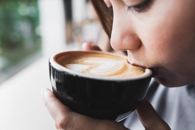 アジアの女性が朝のカフェでカプチーノコーヒーを飲んでいる間近