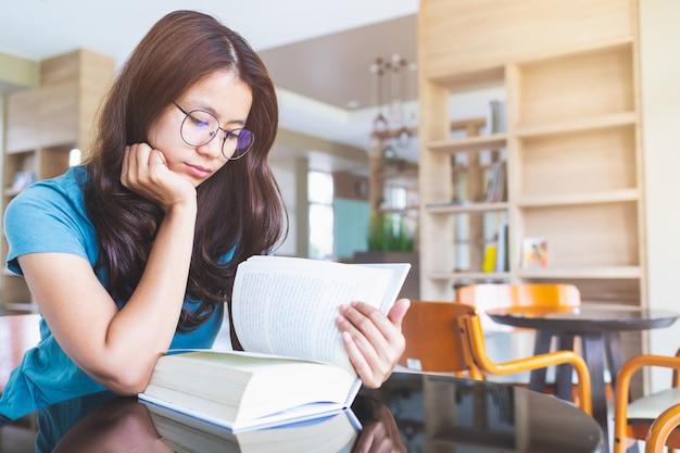 眼鏡をかけているアジアの女性は図書館で本を読んでいます