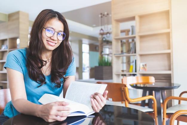 眼鏡をかけているアジアの女性は笑みを浮かべて、図書館で本を読んでいます。