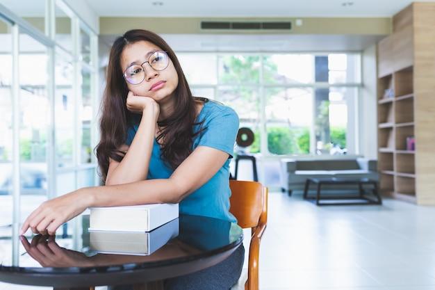 眼鏡をかけているアジアの女性は図書館で本を読んだ後退屈する