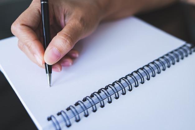 黒いペンを使用してガラステーブルの上の空白のノートブックに書き込む女性のクローズアップ写真