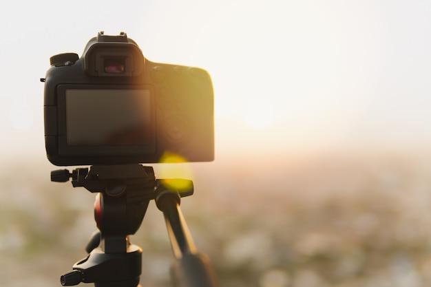 三脚のデジタル一眼レフカメラの後ろに夕日とフレア光の写真を撮る