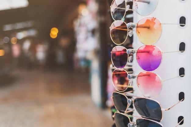 カラフルなサングラスが市場の店の前に一列にぶら下がっています