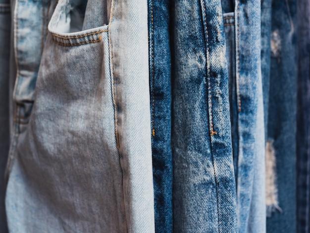 Конец вверх ряда много голубых джинсов висят в магазине